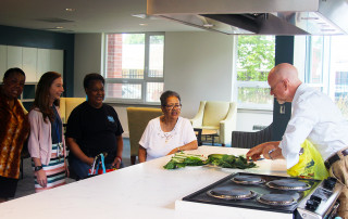 "Wellness center director Edwin Rupert (right) of St. John Neumann Place II (SJNPII) inspects vegetables from the senior housing facility's garden with Ojay Washington, social service coordinator Caroline Morgan, Teresa Thomas and Dale Freeman. One of five senior housing centers, SJNPII recently received the ""Innovation in Design"" award from the Pennsylvania Housing Finance Agency. (Gina Christian)"